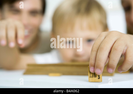 Little boy holding game piece, focus on foreground - Stock Photo