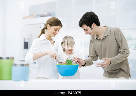 Little girl helping parents cook in kitchen - Stock Photo