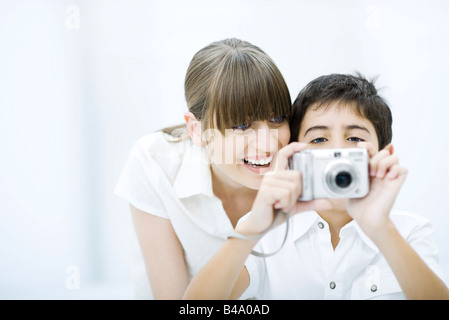 Boy taking picture with camera, mother leaning over his shoulder, smiling - Stock Photo