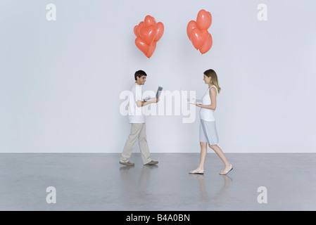 Young man and woman walking toward each other, both carrying laptop computers and heart balloons - Stock Photo