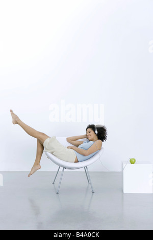 Young woman lounging in chair, listening to headphones connected to apple - Stock Photo