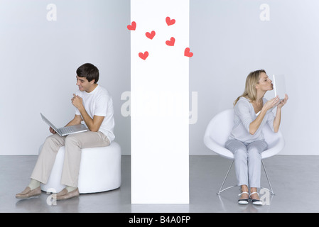 Woman kissing laptop computer, man looking at his own laptop and smiling, hearts in the air between them - Stock Photo