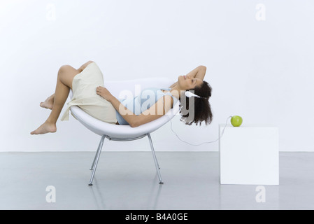 Woman reclining in chair, listening to headphones connected to apple, side view - Stock Photo