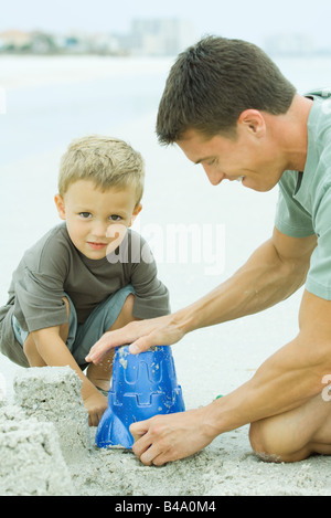 Man making a sand castle with young son - Stock Photo
