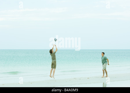 Two men playing volleyball on beach - Stock Photo