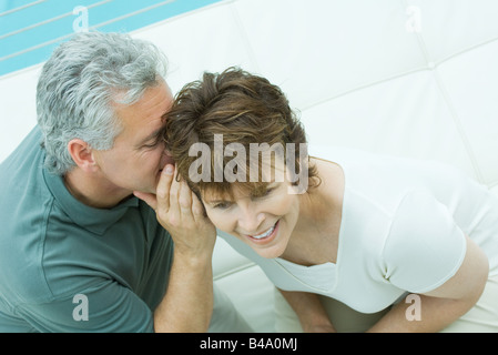 Woman looks away smiling as her husband whispers in her ear - Stock Photo
