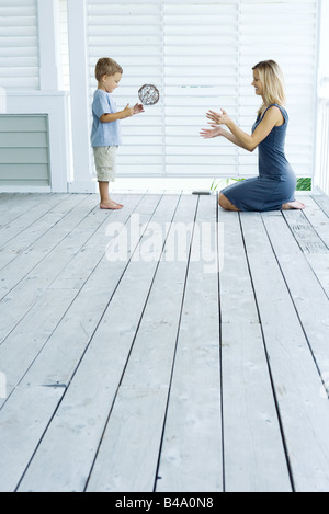 Mother and son playing catch on porch - Stock Photo