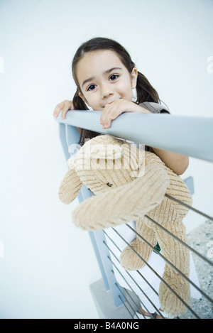 Little girl standing at rail holding teddy bear, smiling at camera - Stock Photo