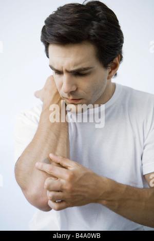 Man putting adhesive bandage on arm, frowning - Stock Photo