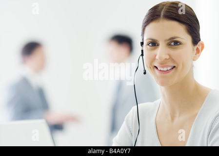 Female telemarketer smiling at camera, portrait - Stock Photo