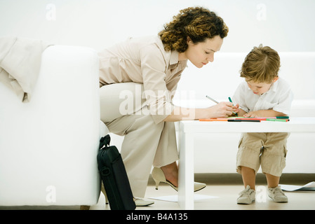 Mother and son coloring together at coffee table - Stock Photo