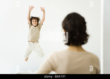 Boy jumping on bed, mother watching from doorway - Stock Photo
