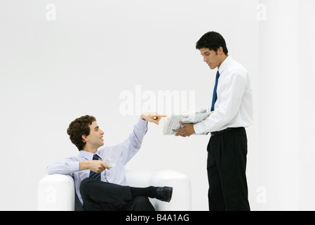 Coworkers on coffee break, discussing newspaper - Stock Photo