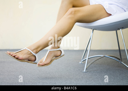 Woman sitting in chair with legs dangling, wearing sandals, cropped view - Stock Photo