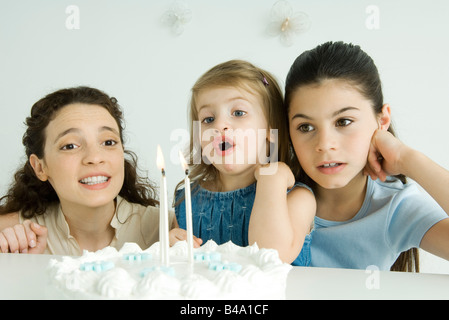 Little girl blowing out candles on birthday cake, mother and older sister watching - Stock Photo