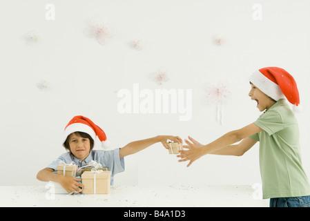 Two boys wearing Santa hats stacking presents, confetti falling around them - Stock Photo