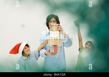 Young man and boys stacking Christmas gifts, smiling, boys wearing Santa hats - Stock Photo