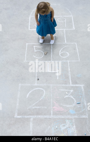 Little girl standing on hopscotch grid, looking down at rock, high angle view - Stock Photo