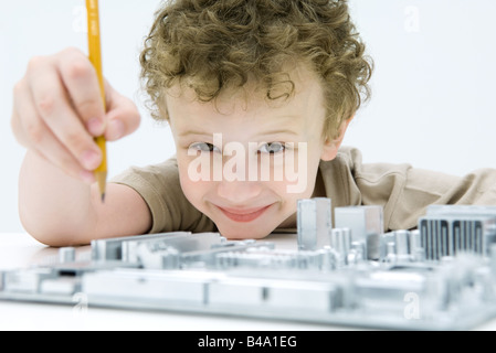 Little boy holding pencil over computer motherboard, smiling at camera - Stock Photo