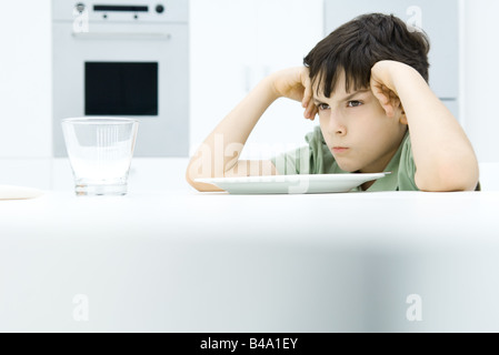 Boy sitting at dinner table, holding head, sulking - Stock Photo