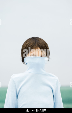 Boy with turtleneck pulled over face, portrait - Stock Photo