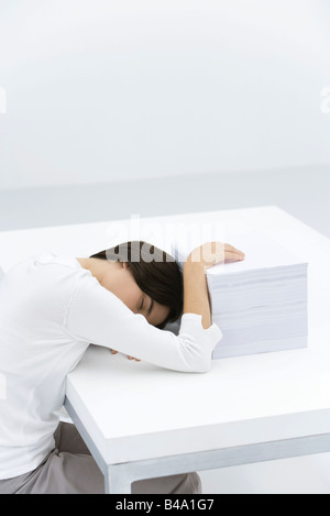 Woman sleeping at desk, hand resting on large stack of papers - Stock Photo