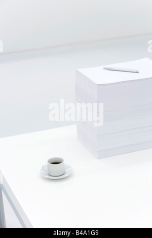 Coffee cup and large stack of documents on desk - Stock Photo