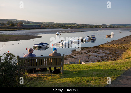 Two men with dogs sitting on a bench beside the Axe estuary in the evening light, Axmouth, East Devon - Stock Photo