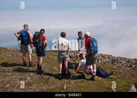 Walkers taking a break on the summit of Slieve Donard, Mourne Mountains, County Down, Northern Ireland - Stock Photo