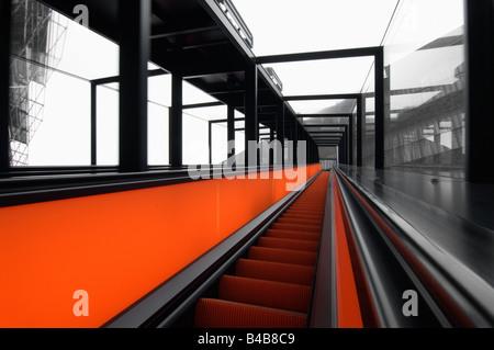 Red lighted escalalator at Weltkulturerbe Zeche Zollverein in Essen Germany - Stock Photo