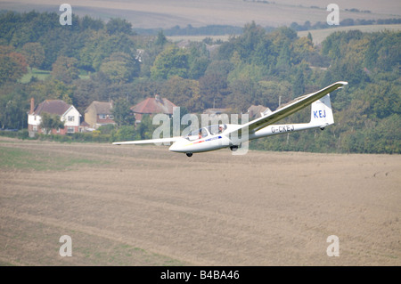Glider flying over crop fields Dunstable Downs England showing a young child up front and an adult behind. - Stock Photo