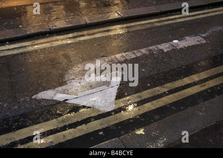 Left-turn traffic arrow and double-yellow no parking lines shine during rain on a wet street in London's West End. - Stock Photo