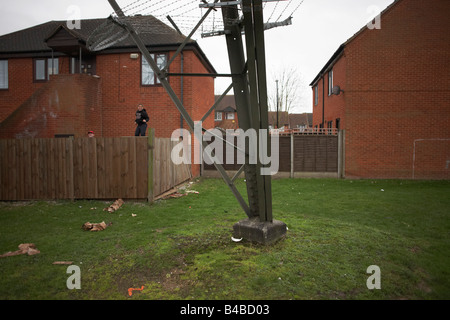 The steel girders of an electricity pylon stands close between housing on an estate in Beckton East London - Stock Photo