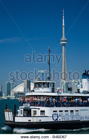 Arriving on the ferry at Toronto Island Park with Rogers Centre and CN Tower in background in Toronto Ontario Canada - Stock Photo