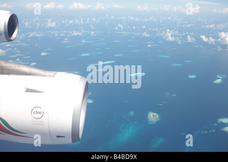 A blue Indian Ocean and remote atolls in the Republic of the Maldives are far below an Airbus's port wing and CFM - Stock Photo