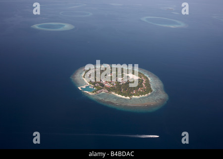 Aerial view of a passing boat and one of 1,192 inhabited and deserted coral islands in the Islamic Republic of Maldives - Stock Photo