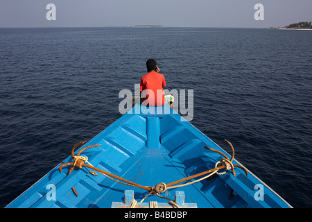 A Maldivian crewman uses a mobile phone after a day's tuna fishing aboard a dhoni fishing boat in a remote area - Stock Photo