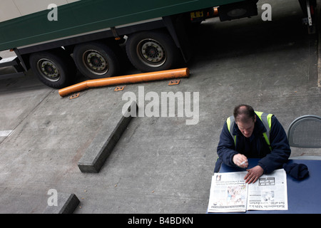 An HGV driver awaits his lorry to be loaded at Sainsbury's 700,000 sq ft supermarket distribution depot loading - Stock Photo