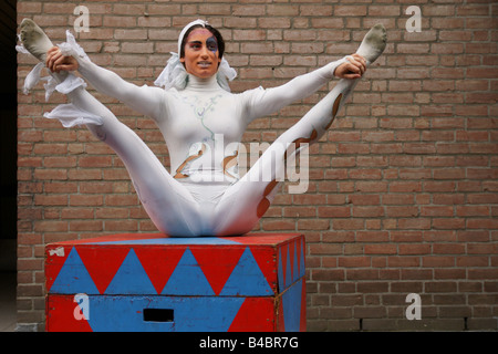 Italian young flexible woman contortionist clown performing show bent whole body smile face one spreading legs outdoors - Stock Photo