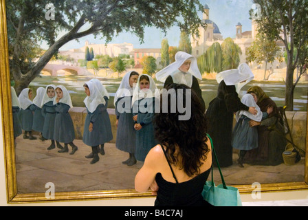 Woman looking at religious oil painting depicting nuns beside the old river Turia at Museum of Fine Arts in Valencia - Stock Photo