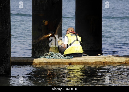 Workman sitting on a small raft using an gas torch to cut and weld a steel pier leg - Stock Photo