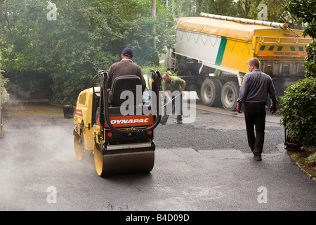 Home improvements gang of workers laying new tarmac domestic drive hot rolling flat - Stock Photo