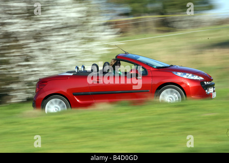 Peugeot 207 CC, model year 2007-, red, driving, side view, country road, open top - Stock Photo