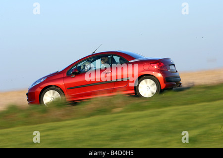 Peugeot 207 CC, model year 2007-, red, driving, side view, country road, closed top - Stock Photo