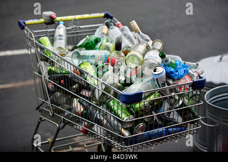 A supermarket trolley full of empty drinks bottles and cans on the pavement outside a flat in Birmingham. - Stock Photo