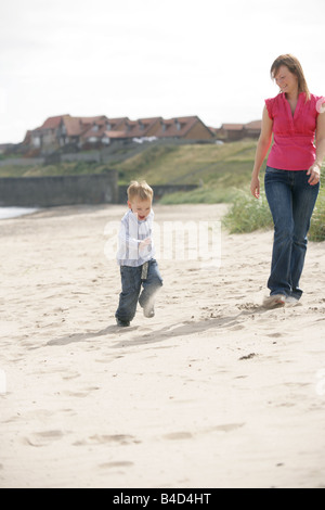 A happy two year old boy running on a beach with his mother walking along side. - Stock Photo
