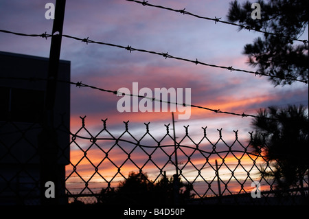 A chain link fence and barbed wire surrounds an industrial warehouse in Cambridge Maryland at sunset - Stock Photo