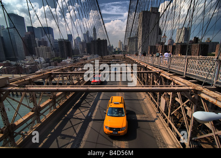 A taxi is among the traffic crossing the Brooklyn Bridge.  Pedestrians can also be seen on the upper walkway. - Stock Photo