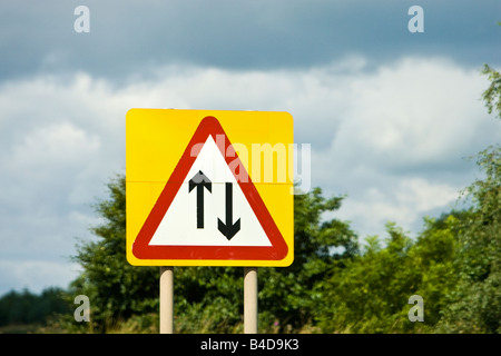 Road sign warning of two way traffic straight ahead England UK - Stock Photo