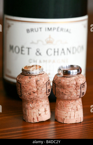Bride and Groom silver white gold platinum wedding rings bands on top of champagne corks in front of champagne bottle - Stock Photo